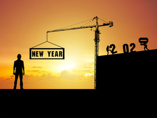 Happy new year 2020 An engineering man standing and watching the work of the workers and the crane Which is installing the letters Happy New Year 2020 at the top of the building
