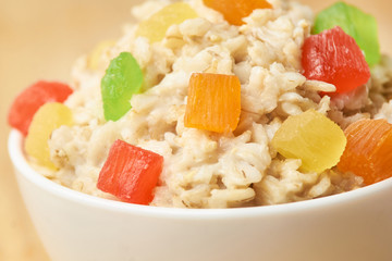 Oatmeal breakfast bowl. Organic healthy food with candied fruit