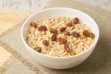 Oatmeal breakfast bowl. Organic healthy food with candied fruit, raisins, nuts