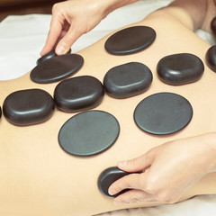 body stone massage. Hot rock masseur. Girl at salon with doctor hands. Relax spa resort