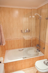 Interior of bathroom with bathtub and shower screen