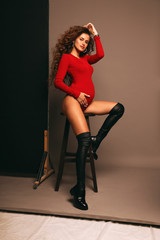 beautiful pregnant woman with dark curly hair in elegant clothes
