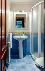 Interior of small bathroom with mirror and shower screen