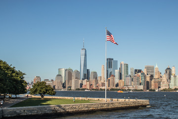 Panorama of New York with Liberty Island in the foreground with a American Flag waving in the wind on a summer day, New York, United States of America.