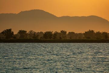 Lake Malawi shore at sunset with orange sky