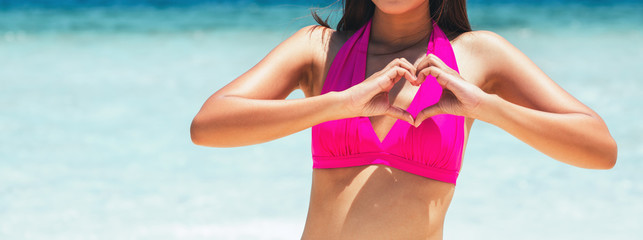 Woman making heart sign on beach in summer