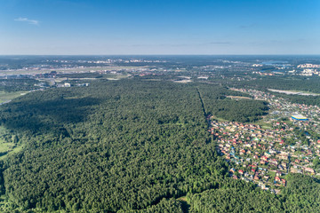 Large green forest. A multi-lane highway runs through the forest. Aerial view, summer sunny day.