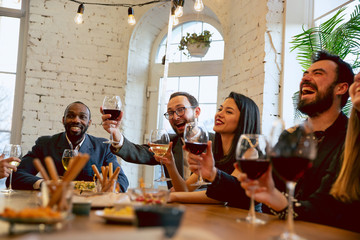 Happy co-workers celebrating while company party, corporate event. Young caucasian people in...