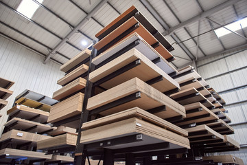 A large industrial racking in a woodworking diy factory,  holding and storing various wooden laminate plywood chipboard boards. wood work carpentry and diy unsustainable building materials.