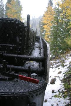Steam locomotive details on a rainy, snowy day