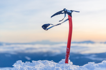 Expedition equipment for winter climbing - ice-axe in natural conditions at stunning sunset scene in mountains background.