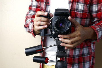 Adult man holding an old and vintage medium format film camera on a tripod.