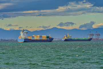 Sea transportation dry cargo vessels moored on open sea, with low waves. Day view of freighter merchant bulk ship and container carriers at Thermaic Gulf outside port of Thessaloniki, Greece.