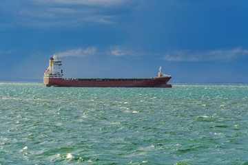 Sea transportation dry cargo vessel moored on open sea, with low waves. Day view of freighter merchant bulk ship carrier at Thermaic Gulf outside port of Thessaloniki, Greece.