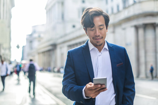 Handsome businessman walking in the street, using his phone