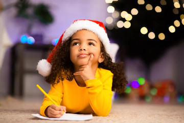 Wistful little afro girl thinking about letter to Santa Claus