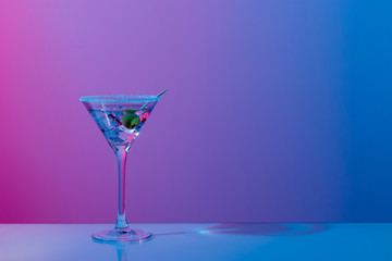Martini cocktail with ice cubes, olive, sugar rim in neon pink and blue light on mirror bar. Night club, party, cocktail menu concept. Close-up, copy space