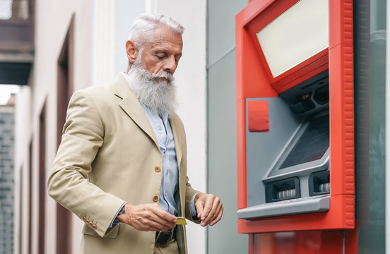 Senior man withdraw money from bank cash machine with debit card - Bearded hipster mature male doing payment with credit card in ATM - Concept of business, banking account and elderly lifestyle people