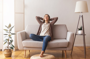 Stores photo Detente Millennial girl relaxing at home on couch, enjoying free time