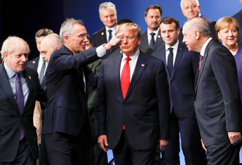 NATO Secretary General Jens Stoltenberg directs NATO Alliance leaders to leave the stage after family photo during the annual NATO heads of government summit at the Grove Hotel in Watford