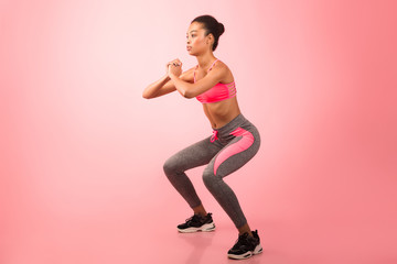 Afro Girl Doing Deep Squat Exercise Over Pink Background