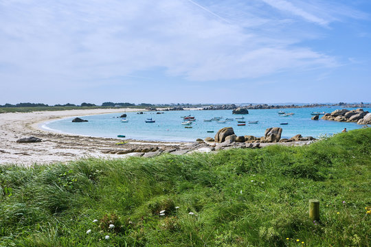 View to an idyllic small bay with grass, sand and little rocks, small boats in the water, summer holiday feeling