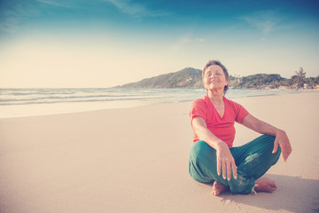 Beautiful mature woman 50 years old resting in lotus position on the beach by the sea. Active lifestyle, travel and sport for senior citizens