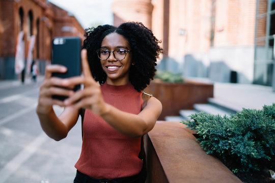 Optimistic African American tourist taking selfie exploring city