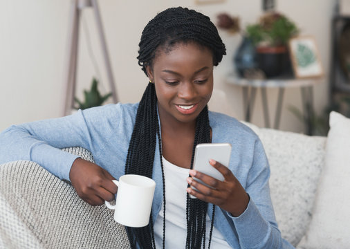 Young african american girl reading message on smartphone and drinking coffee
