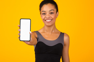 Fit Black Girl Showing Phone Blank Screen Standing, Yellow Background