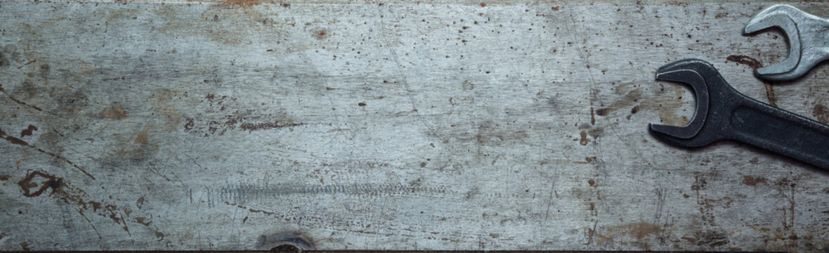 Steel textured metal sheet with rust and wrenches laid out on it. Background banner. Top view with copy space. Flat lay