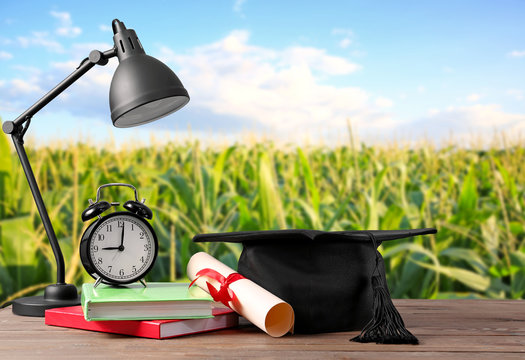 Mortar board, diploma, lamp, clock and books on table. Concept of high school graduation