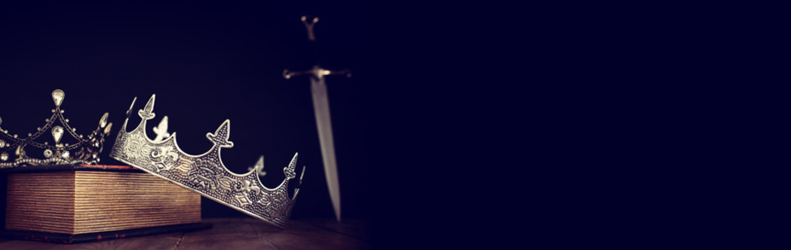 low key image of beautiful queen/king crown over antique book next to sword. fantasy medieval period. Selective focus