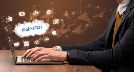 Businessman working on laptop with HIGH-TECH inscription, modern technology concept