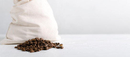 Pile of roasted coffee beans, white bag full of coffee beans on the bright surface against bright wall.Free space for design