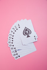 Expanded playing cards on pink background