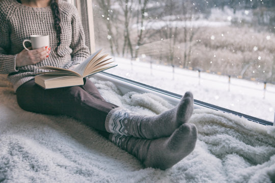 Woman sitting by the window reading book drinking coffee. Winter snowing landscape outside