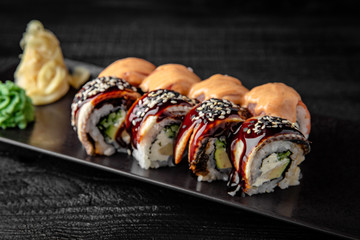 Sushi roll (Maguro) salmon, smoked eel, avocado, philadelphia cheese on black background. Sushi menu. Japanese food.