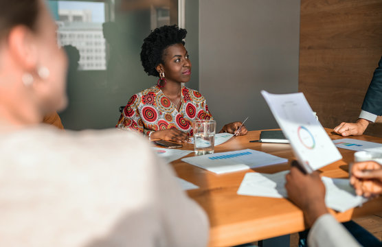 Beautiful young confident professional black african millennial business woman in boardroom meeting. Wearing traditional clothing