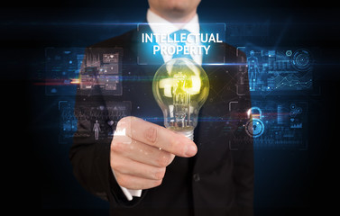 Businessman holding lightbulb with INTELLECTUAL PROPERTY inscription, online security idea concept