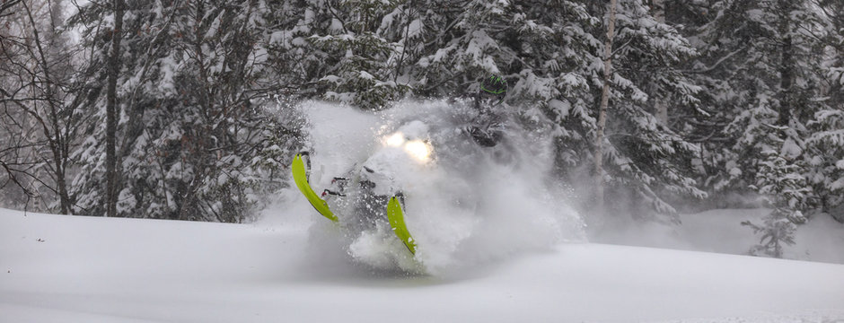 snowmobile rider makes a turn and jump during a snowfall. in the winter forest, leaving behind a trail of big splashes of white snow from a snow bike. bright snowmobile and black suit. snowmobilers