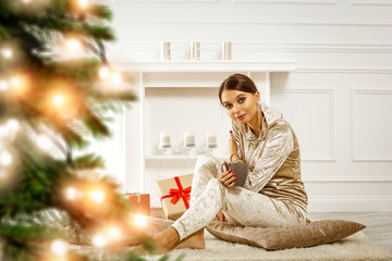 Beautiful young brunette in golden Christmas fashionable sweat suit.Christmas tree and presents.Interior of luxury apartment with ecological fireplace.Decorating candles and Christmas lights.Copy spac