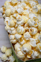 Green paper box with sweet popcorn ready to eat