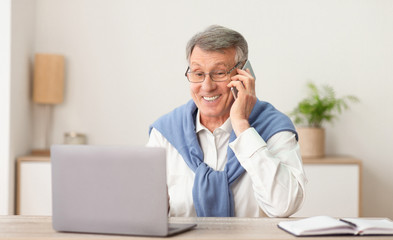 Elderly Man Talking On Phone Working On Laptop At Workplace