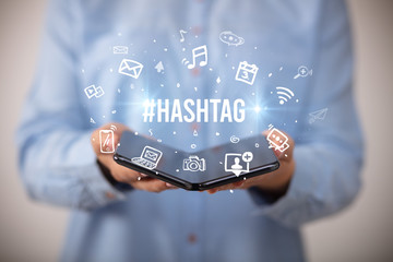 Businessman holding a foldable smartphone with #HASHTAG inscription, social media concept