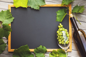 Wine business concept with copy space. Top view of a bottle, a glass with grapes and a chalk board