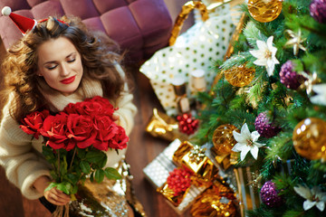 smiling trendy middle age woman enjoying red roses