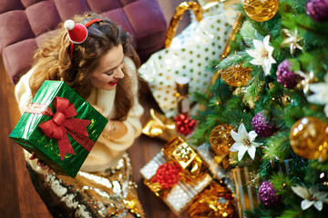 happy young woman shaking green Christmas present box