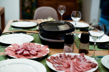 Raclette table setting with cheese and delicatessen