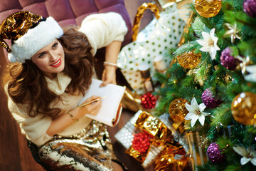 smiling trendy middle age housewife with notebook making list